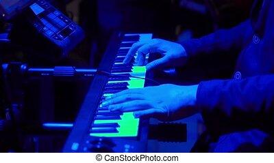 Musician man play keyboard on dark stage