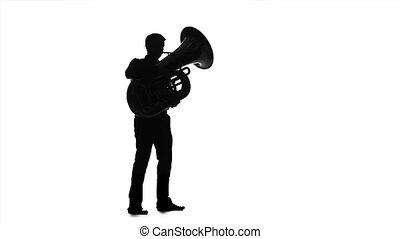 Musician man playing on tuba in slow motion. Black silhouette