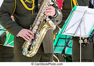 musician of military orchestra plays saxophone