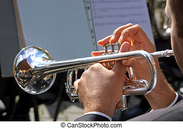 Musician playing on silver trumpet in street orchestra
