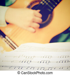 Musician playing classical guitar with musical chords, retro filter effect