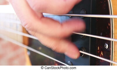 Musician playing electric bass guitar outdoors in closeup...