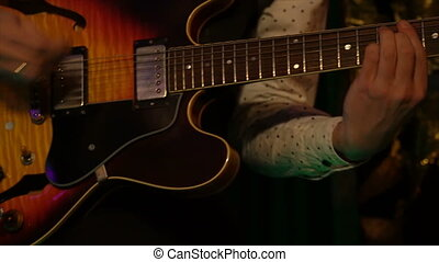 Musician playing electric guitar melody at stage