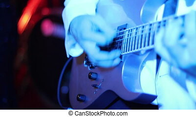 musician playing guitar in a disco lights