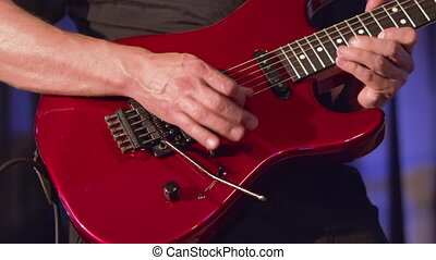 Musician playing red electric guitar on stage. - Musician...