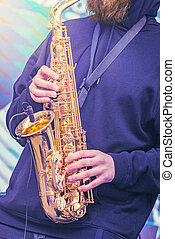 Musician playing saxophone at evening time on the city square.