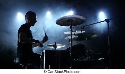 Musician plays a melody on the drums. Black smoke background. Side view. Silhouettes. Slow motion