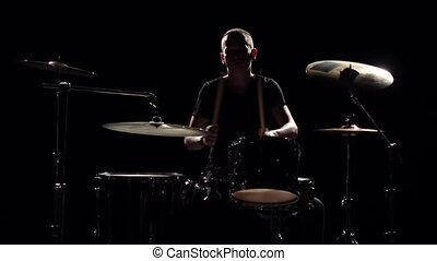 Musician plays professionally good music on drums using sticks. Black background. Silhouette. Slow motion