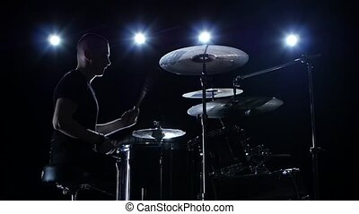 Musician plays professionally music on drums. Black background. Side view. Back light. Silhouette. Slow motion