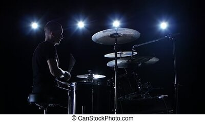 Musician plays professionally music on drums. Black background. Side view. Back light. Silhouette