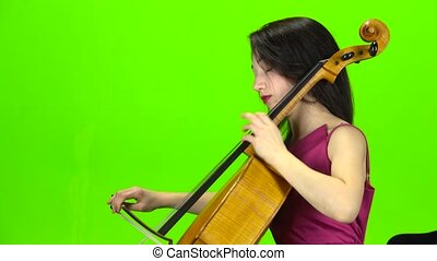 Musician plays the cello professionally. Green screen. Side...