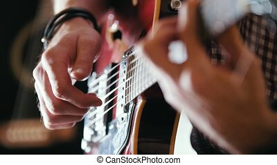 Musician plays the guitar, hands close up, art concept