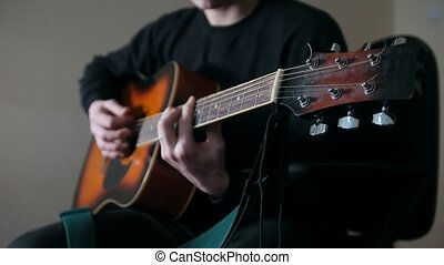 Musician plays the guitar, hands close up