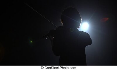 Musician plays the violin while standing with his back glare...