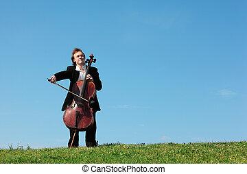 musician plays violoncello against sky