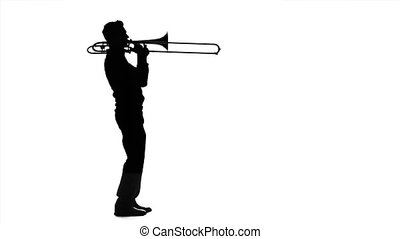 Musician professional playing on trombone in slow motion. Black silhouette