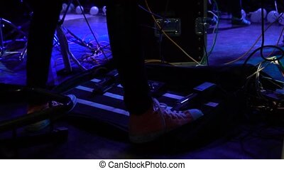 Musician pushes his foot on the sound amplifier for guitar