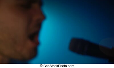 Musician sings into a microphone