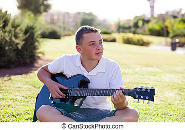 musician sits on the grass with an electric guitar