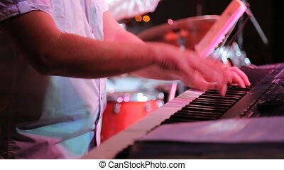 Musician skilfully plays on synthesizer during night party.