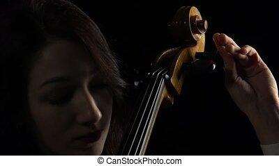 Musician tunes a cello. Black background. Close up -...