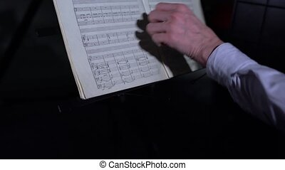 Musician turning page of music book, close-up - View on...
