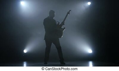 Musician virtuoso pluck the strings on a bass guitar. Slow motion