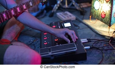 musician with a guitar in his hands twists the handle electronic mixer device