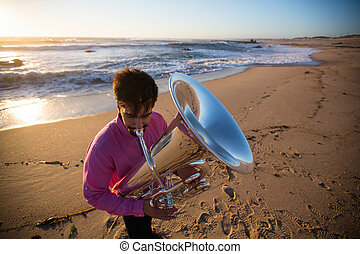 Musician with a tuba playing on the sea beach.