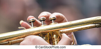 Musician with brass trumpet plays classical music. His fingers press the valves to give the best sound. Close up view with details, blurred background, banner.