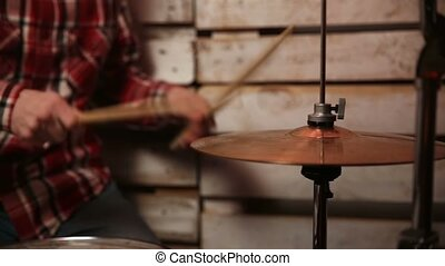 Musician with drumsticks playing drums and cymbals