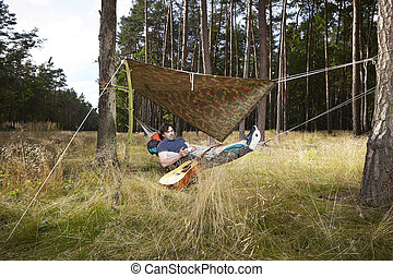 Musician with guitar in forest laying in hammock bed