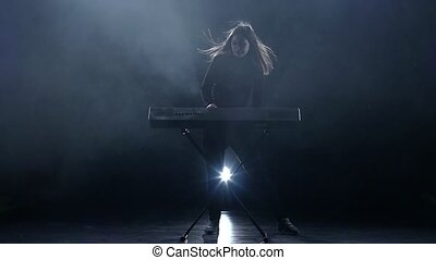 Musician woman playing the piano. Dark background. Slow motion