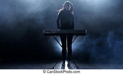 Musician woman playing the piano. Studio. Smoke