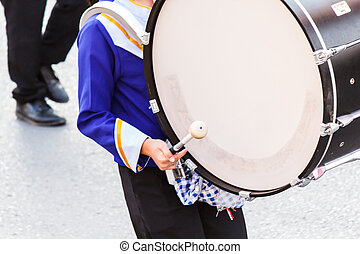 Musicians march in blue and white uniform playing large bass drums in a march