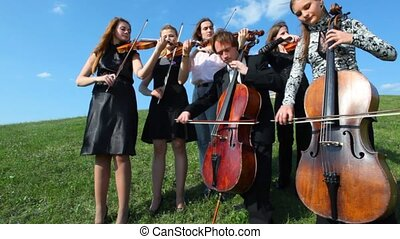 six musicians plays very old classical music on stringed instruments stands on grass