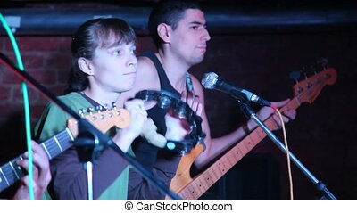 musicians with guitars and tambourine live on stage