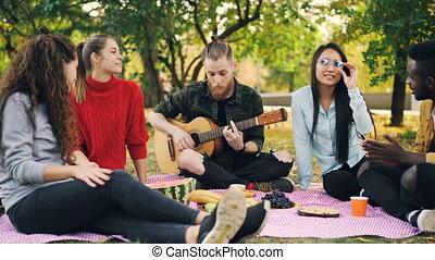 musique, gens, chant, applaudir, séance, parc, couverture, nourriture, guitare jouer, hipster, amusant, amusement, concept., amis, joyeux, hands.