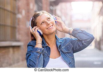 musique, heureux, portrait, girl, écoute, sans fil, écouteurs, rue