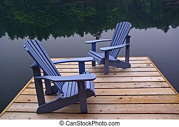 Two traditional Muskoka chairs on a dock overlooking still lake waters in Northern Ontario