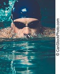 muskulös, junger mann, in, blaue kappe, in, schwimmbad
