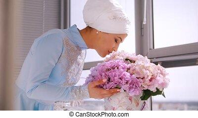 Muslim bride in blue wedding dress for nikah, smelling flowers