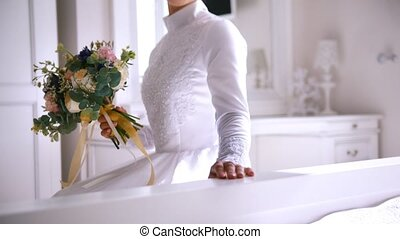 Muslim bride in white wedding dress and birdal headdress with bouquet of flowers