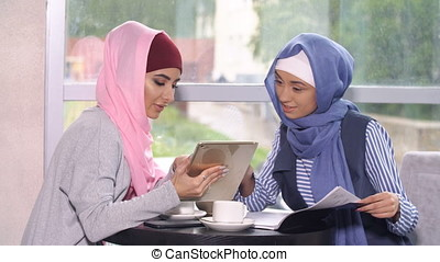 Muslim business woman at a business meeting in a cafe.