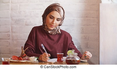 Muslim Business Woman Working Documents in Cafe.