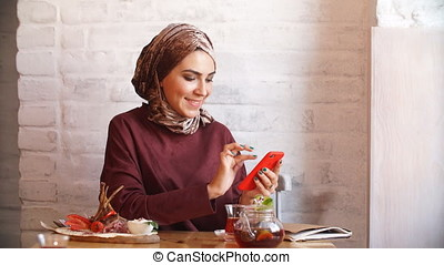 Muslim Business Woman Working on Mobile Phone in Cafe.
