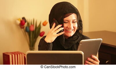 Muslim businesswoman sitting in the office and talking on...