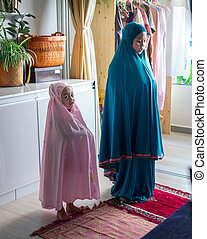 Muslim children praying at home. Learning to pray for the little girl. Happy and jovial child.