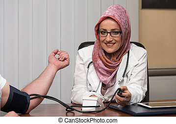 Muslim Doctor Taking Young Man's Blood Pressure