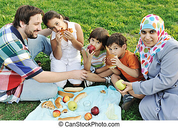 Muslim family, mother and father with three children together in nature sitting and eating on green grass: picnic